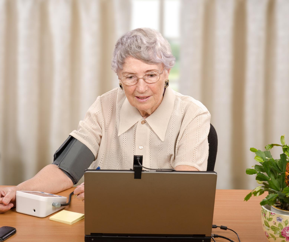 woman with gray hair takes own blood pressure, looks at laptop screen